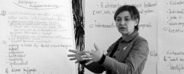Teilnehmerin beschreibt methodische Schritte vor mehreren Flipcharts