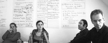 Vier Klausurteilnehmer an einem Besprechungstisch, im Hintergrund Flipcharts mit Ergebnissen