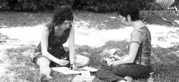 Zwei Frauen erarbeiten ein Konzept in der Wiese sitzend