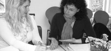 Zwei Teilnehmerinnen diskutieren und schreiben auf Kaertchen